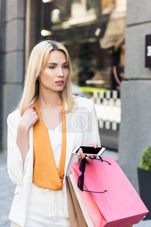 attractive blonde woman with sunglasses, smartphone and shopping bags looking away on street