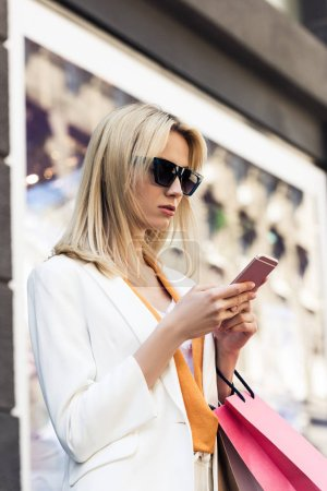beautiful stylish blonde girl in sunglasses holding shopping bags and using smartphone