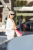 beautiful blonde girl in sunglasses holding smartphone and shopping bags, smiling at camera on street
