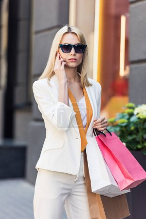 fashionable young woman in sunglasses holding paper bags and talking by smartphone on street