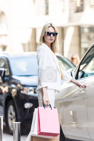 stylish young woman in sunglasses holding shopping bags and opening car
