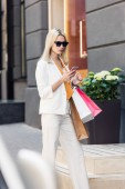selective focus of fashionable young woman in sunglasses holding paper bags and using smartphone on street