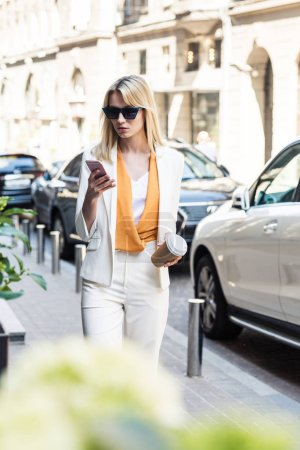beautiful young woman in sunglasses holding disposable coffee cup and using smartphone while walking on street