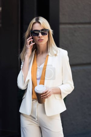stylish young woman holding disposable coffee cup and talking by smartphone on street