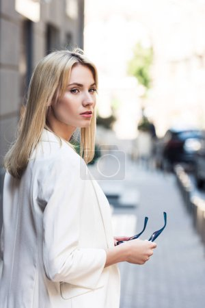 Photo for Beautiful stylish young blonde woman holding sunglasses on street - Royalty Free Image
