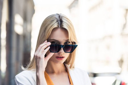 portrait of beautiful young blonde woman adjusting sunglasses and looking at camera