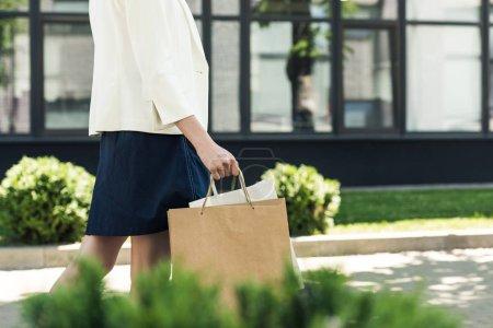 Photo pour Plan recadré de jeune femme tenant des sacs à provisions et marchant dans la rue - image libre de droit
