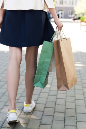 low section of young woman with shopping bags walking on street