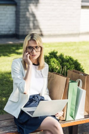 attractive stylish girl talking by smartphone and using laptop while sitting on bench with paper bags