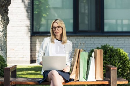 young blonde woman in eyeglasses using laptop while sitting on bench with shopping bags