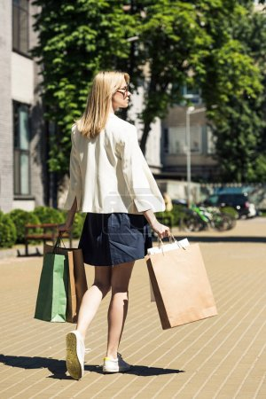 back view of stylish blonde girl with shopping bags walking on street