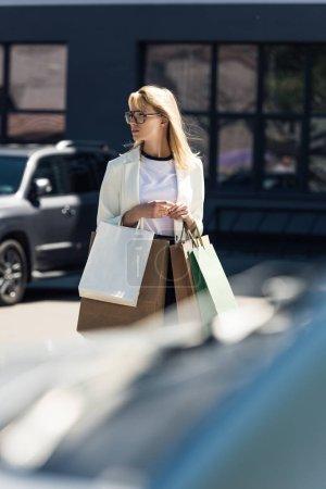 Photo pour Foyer sélectif de la jeune femme blonde avec des sacs à provisions marche sur le parking - image libre de droit
