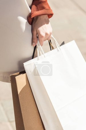 close-up partial view of young woman holding shopping bags in hand