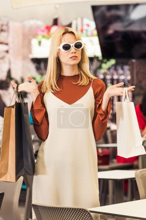 beautiful stylish young woman in sunglasses holding shopping bags in boutique