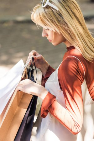 young blonde woman holding shopping bags on street