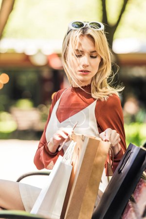 beautiful young woman sitting on bench and looking into shopping bag