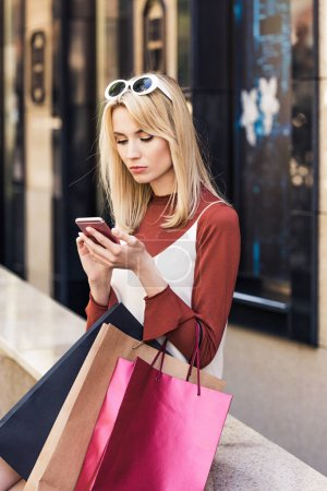 Photo for Beautiful stylish young woman holding shopping bags and using smartphone - Royalty Free Image
