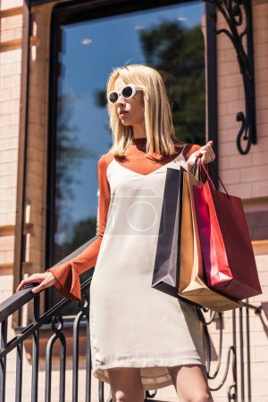 low angle view of stylish young blonde woman in sunglasses holding shopping bags on street