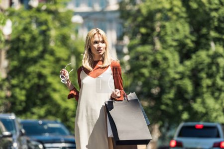 beautiful stylish blonde girl with sunglasss and shopping bags looking away on street