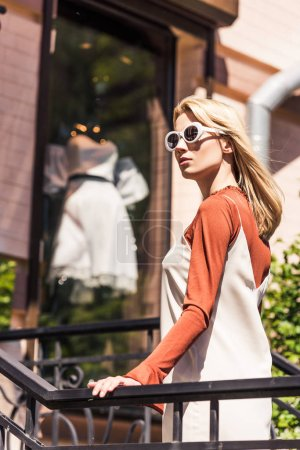 beautiful young woman in sunglasses looking away while standing near fashionable boutique