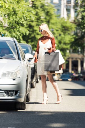 full length view of stylish young woman with paper bags opening car on parking