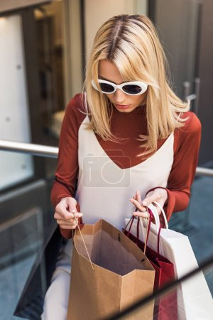 beautiful young blonde woman in sunglasses looking into shopping bag