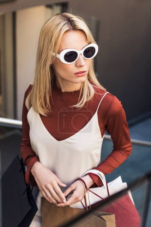 high angle view of beautiful young woman in sunglasses holding paper bags and looking away