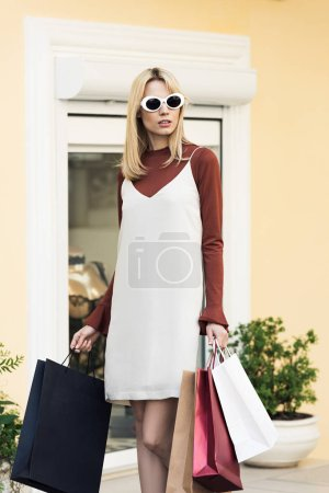 beautiful young blonde woman in sunglasses holding shopping bags on street