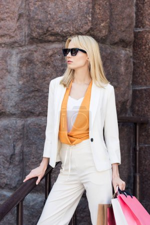 beautiful fashionable blonde woman in sunglasses holding shopping bags and looking away on street