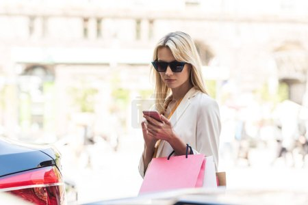 beautiful stylish blonde woman in sunglasses holding paper bags and using smartphone on street