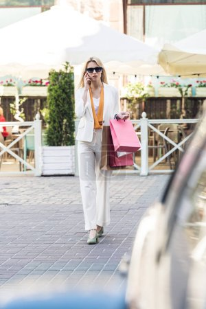 Photo for Selective focus of stylish blonde woman with shopping bags and smartphone walking on street - Royalty Free Image