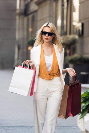 beautiful stylish blonde woman holding shopping bags and walking on street