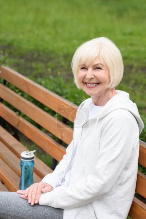 smiling elderly woman in sportswear sitting on bench with sport bottle of water