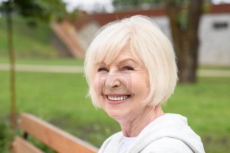 Photo for Portrait of cheerful senior woman sitting on bench in park - Royalty Free Image