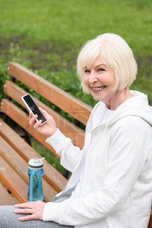 elderly cheerful woman using smartphone while sitting on bench with sport bottle of water