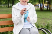cropped view of smiling senior woman holding sport bottle