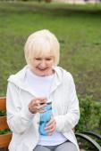 smiling senior woman holding sport bottle of water