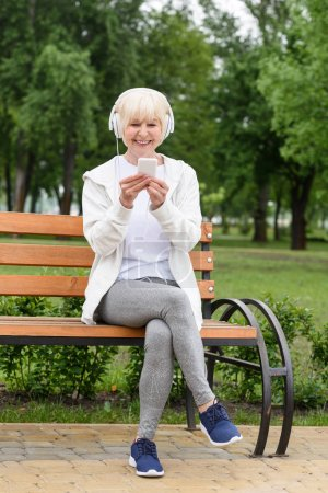 cheerful elderly woman listening music with headphones and smartphone while sitting on bench in park