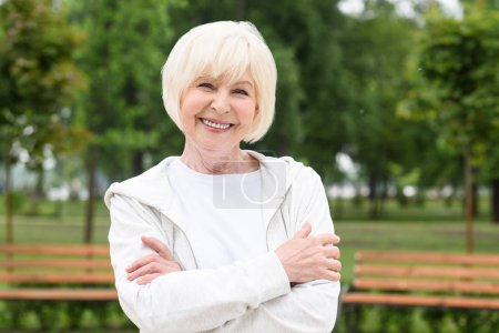 smiling senior woman with crossed arms standing in park
