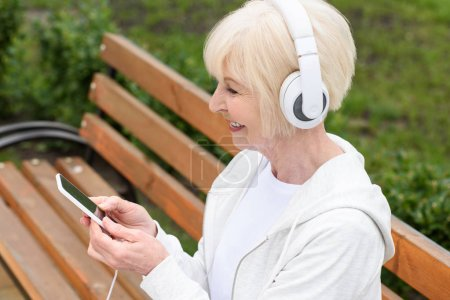 smiling elderly woman listening music with headphones and smartphone