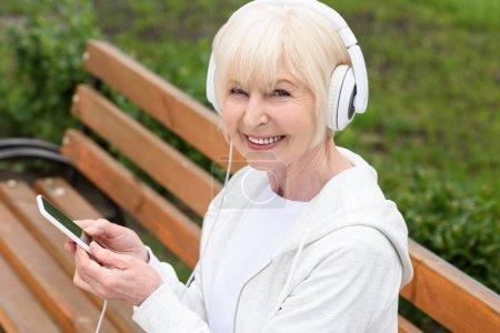 escuchar música feliz mujer senior con auriculares y smartphone