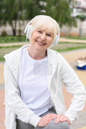 smiling elderly woman listening music in headphones
