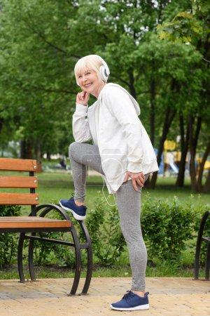 elderly sportswoman in headphones training in park