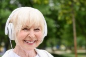 happy senior woman listening music in headphones