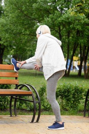Photo pour Haute femme athlétique dans les écouteurs qui s'étend près de banc dans le parc - image libre de droit