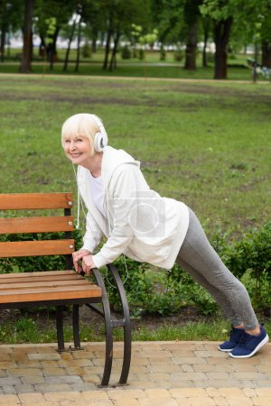 senior sportswoman in headphones doing push up near bench in park