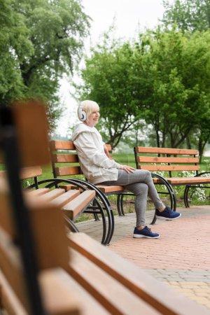 senior woman listening music in headphones on bench in park