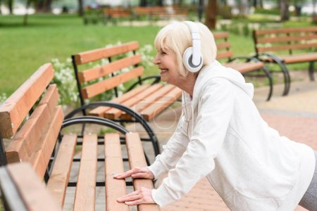 senior sportive woman in headphones training near benches in park