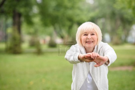 elderly sportswoman exercising on green lawn in park