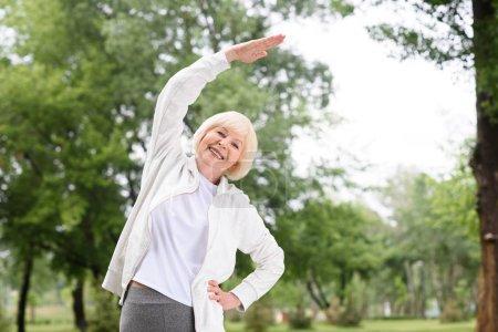 vieille femme Sportswear exercer et qui s'étend dans le parc